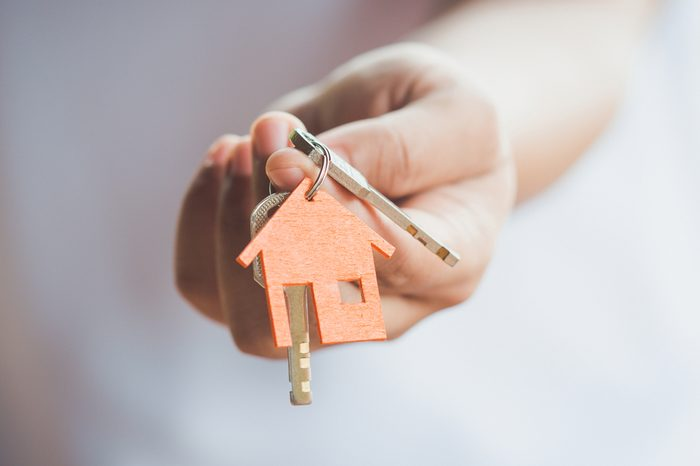 Female hand holding house key,real estate agent.