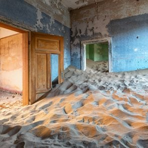 Abandoned building being taken over by encroaching sand, Kolmanskop ghost town, Namib Desert