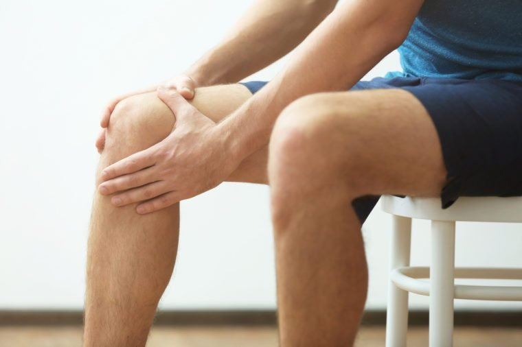 Young man suffering from knee pain at home, closeup
