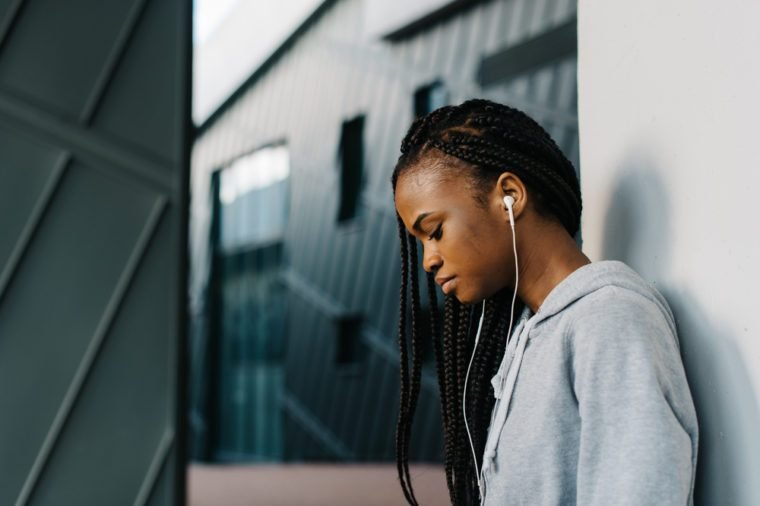 Close-up profile portrait of young african american woman leaning against a wall, listening music with headphones, eyes closed