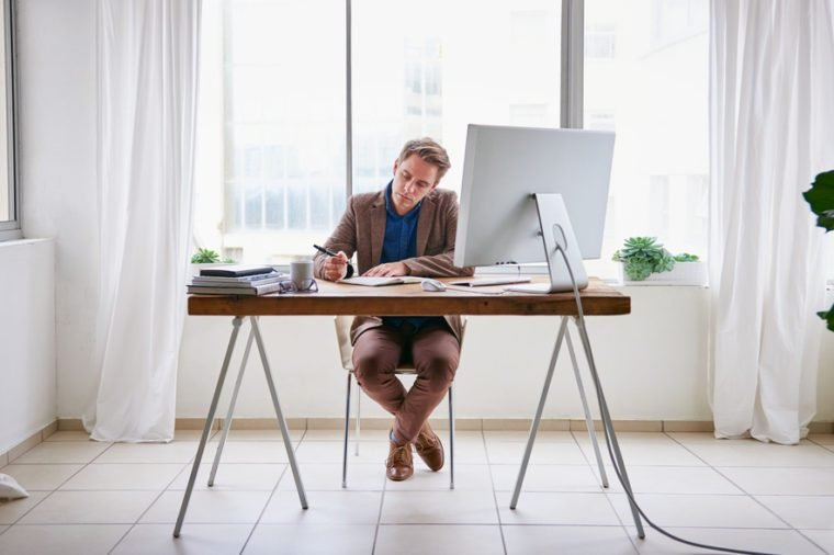 Full length image of a young male entrepreneur sitting at his desk in a contemporary work space for one person and writing in his journal