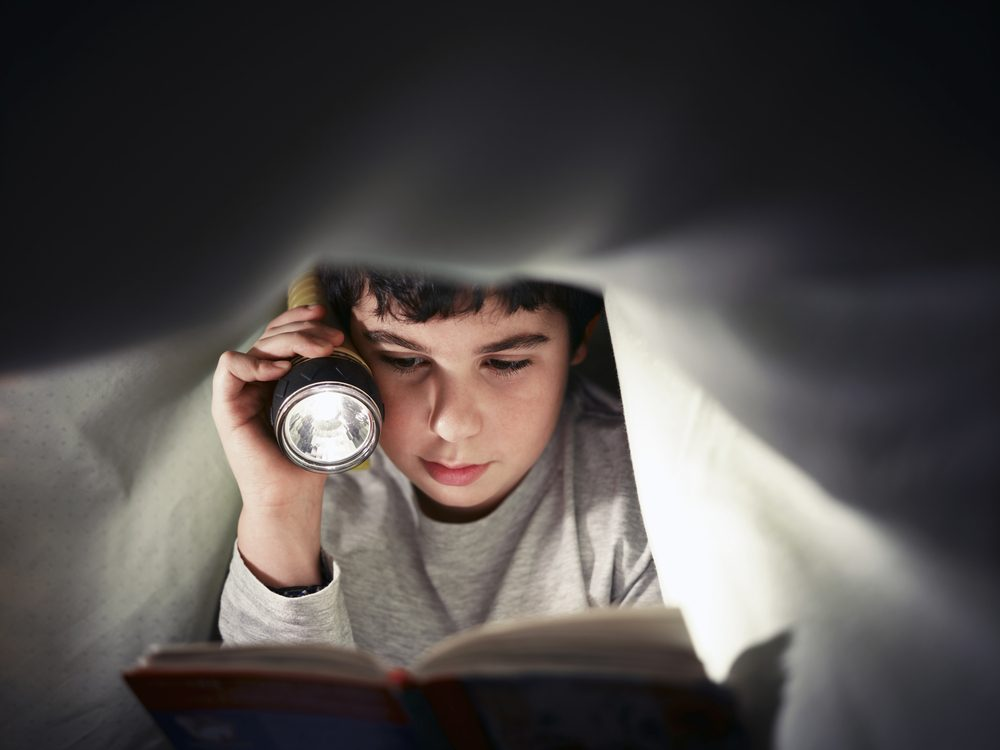 caucasian child reading book under the covers at night. Front view, copy space