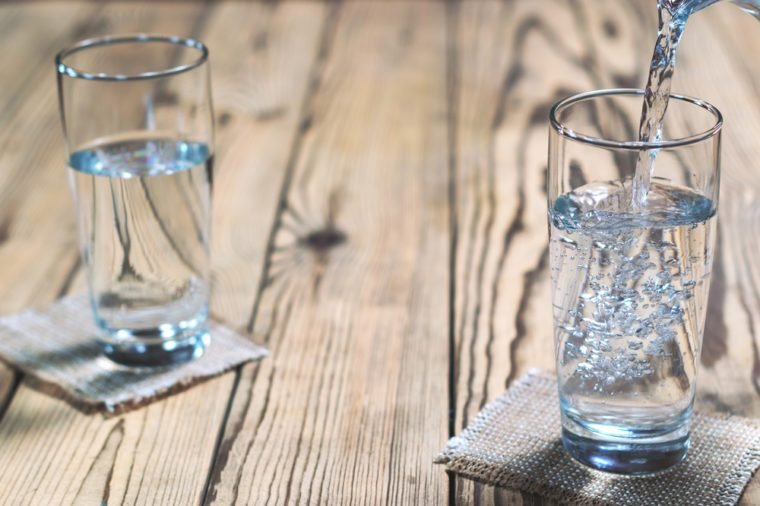 Glasses of water on a wooden table. Water was poured into the beaker. Selective focus on right glass. Shallow DOF