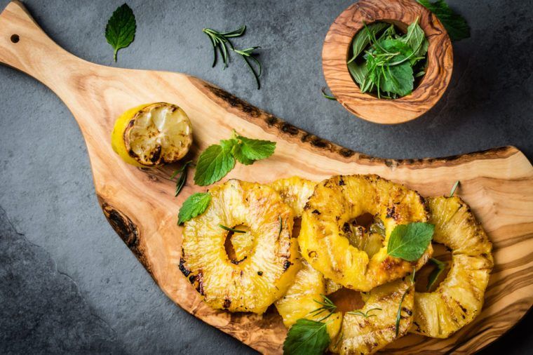 Grilled pineapple slices with fresh mint on olive wooden cutting board, gray slate background. top view