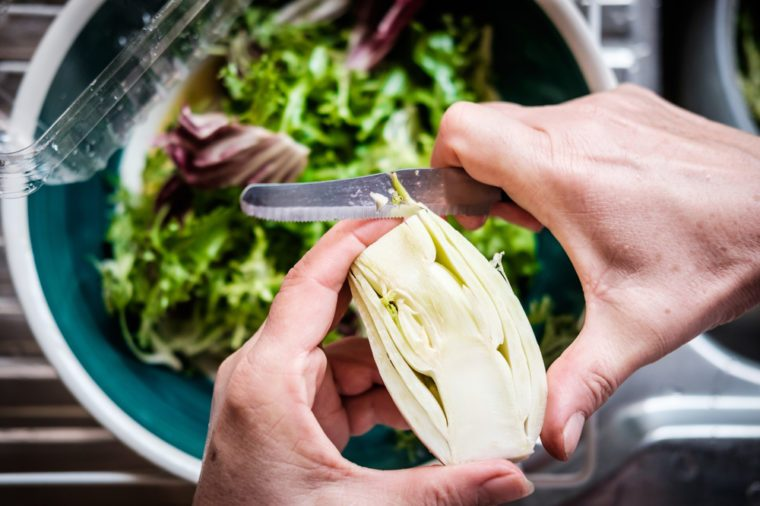 Middle aged female hands cutting fennel over salad bowl. Top down view.