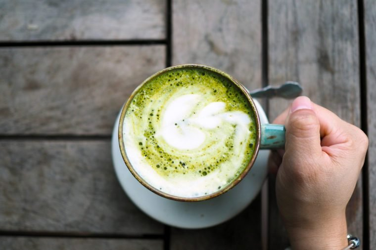 A ceramic cup of Japanese matcha latte with beautiful latte art on wooden table. Selective focus.