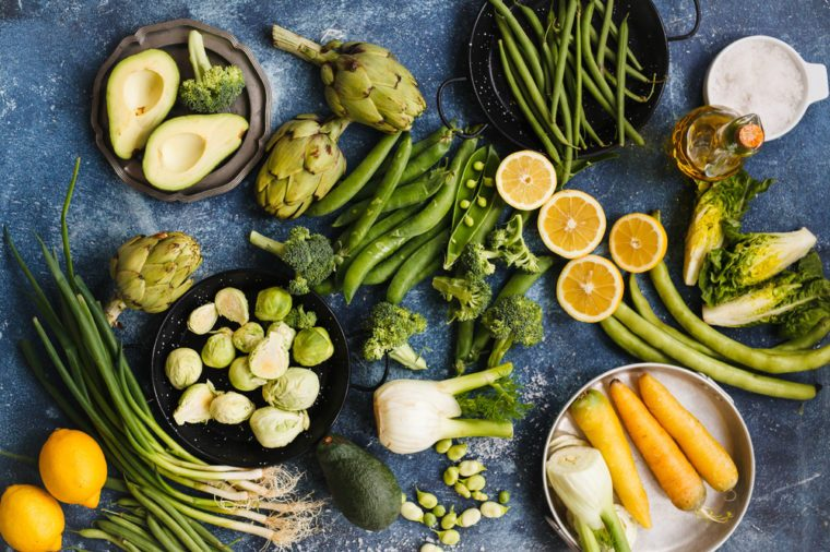 Greenery veggies composition. Variety of green vegetables and lemons. Top view.