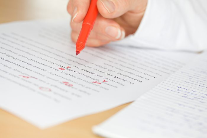 Proofreader with red pen checks a transcription of some hand written text