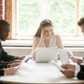Serious multiracial businessmen holding documents at meeting with businesswoman, male diverse entrepreneurs considering new contract with female partner, employees reading woman boss instructions