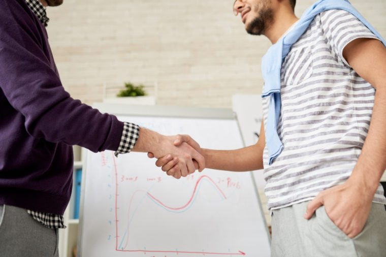 Mid-section portrait of two unrecognizable businessmen shaking hands against whiteboard with statistics graph in modern office