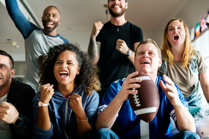 Friends cheering sport league together