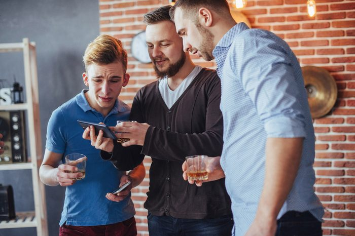 Cheerful old friends communicate with each other and phone watch, with glasses of whiskey in pub. Concept of entertainment and lifestyle. Wifi connected people in bar table meeting.