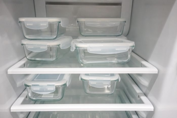 Glass food containers with white plastic lid in new open refrigerator.