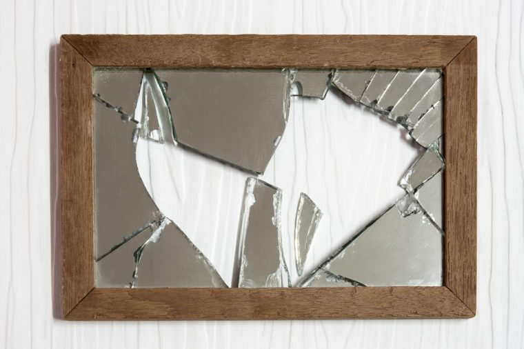 Broken mirror on white wooden