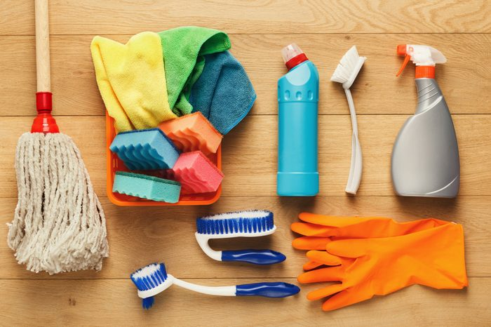 Spring cleaning background. Assortment of colorful spray detergents, sponges, rags and other supplies on wooden table, top view. Cleaning services and tidying up concept