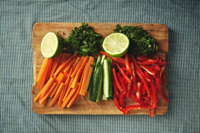 Colorful fresh chopped carrots, cucumbers and bell peppers with herbs and lime on rustic wooden board on a blue and white checkered napkin