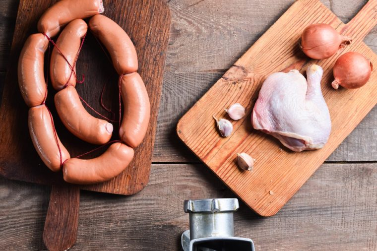 Mincer, chicken, sausage, on a wooden table. The process of making sausage at home.
