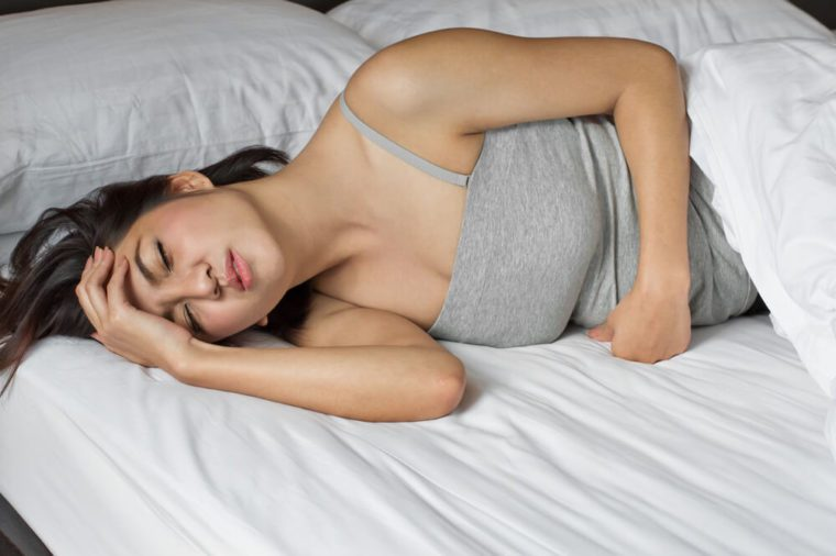 sick woman on bed concept of stomachache, headache, hangover, sleeplessness or insomnia