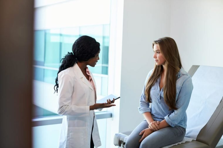 Female Doctor Meeting With Teenage Patient In Exam Room