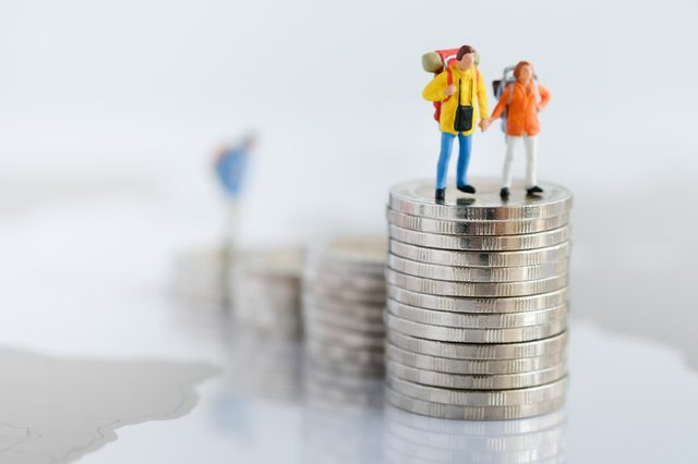 Miniature people: Two backpacker standing on rows of stack coins using as background Money, Financial, Business Growth and travel concept,