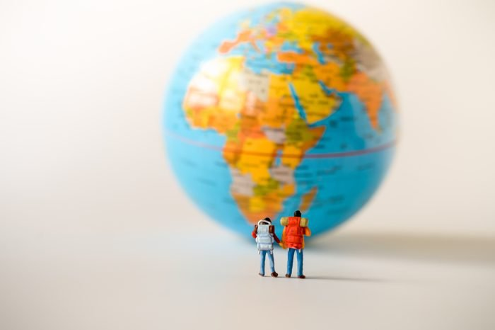 Miniature people: traveler mini figures with backpack standing looking at Global World map balloon. Success Business Due around the world and Traveling agency concepts