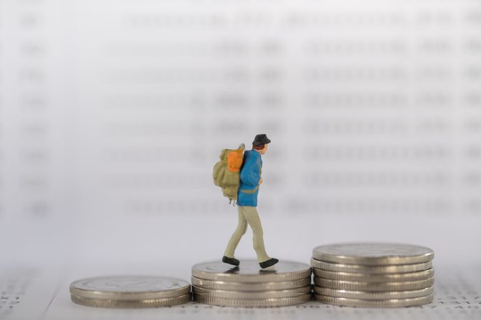 Business , travel and money concept. Traveler miniature figure with backpack walking on stack of coins on bank passbook as background.