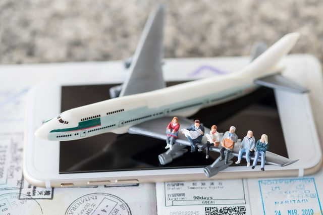 Travel Concept. Group of traveler siting and waiting on airplane wing on smart phone and passport with immigration stamps