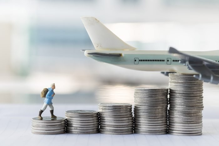 Travel saving and planing concept. Traveler miniature people figure with backpack walking to top of stack of coins with airplane model on top.