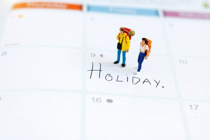 """Miniature people: Backpacker standing on calendar with text """"HOLIDAY"""". Travel on holiday and business concept."""