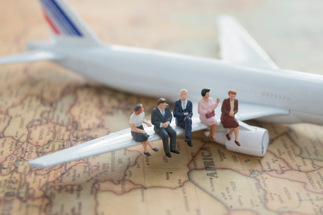Miniature people : business team sitting on airplane wing for travel around the world, using as business trip traveler adviser agency or explorer on earth background concept.