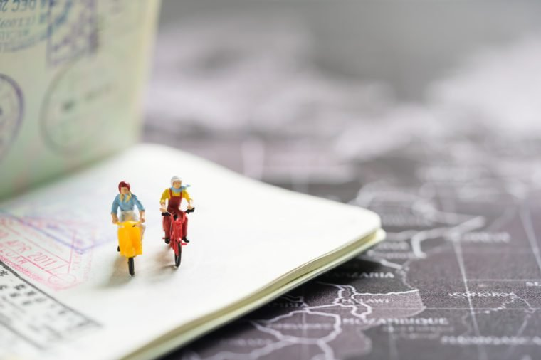 Miniature people with traveling concepts. Group of travelers riding bicycles on passport with stamps. Concept of traveling or exploring the world, budget travel