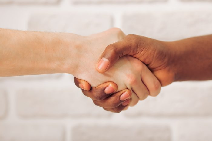Handshake of Afro American and caucasian male hands, against white brick wall, close up