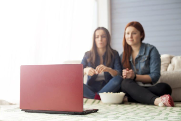 Two girl friends sitting on the floor near the couch in front of them there is a computer on which they watch a movie and eat popcorn. Funny friends relaxing together.