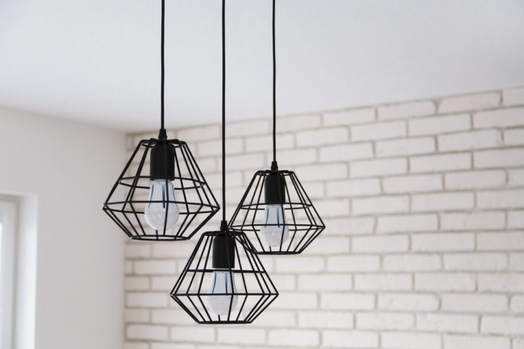 A modern loft chandelier made of black wire in a stylish white interior.