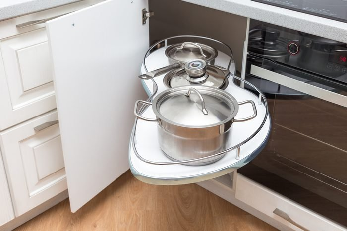 Solution for a kitchen corner storage in a cupboard. A corner unit with pullout shelves for cookware.
