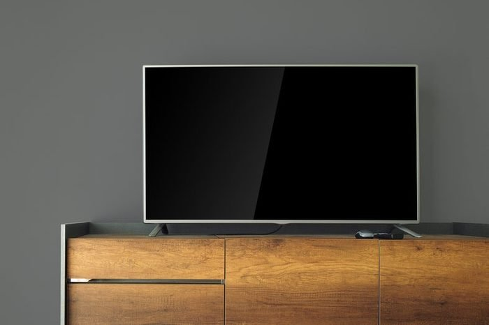 Led TV on TV stand with black wall