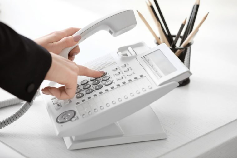 Woman using landline phone in office, closeup