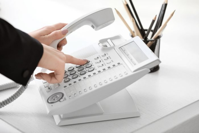 Woman using landline phone in office, closeup