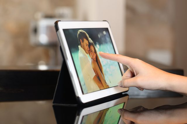 Woman hand using a tablet watching photos and touching screen at home