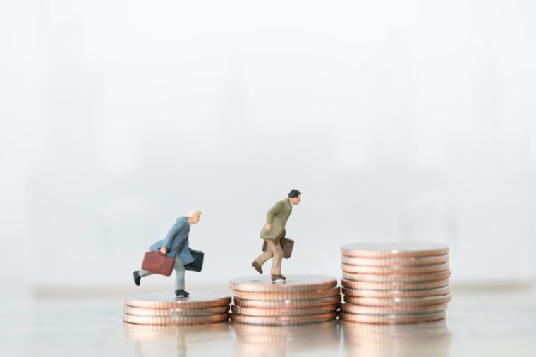 Miniature people: small figures businessmen walking and running on top of coins. Money, Financial, Business Growth concept.