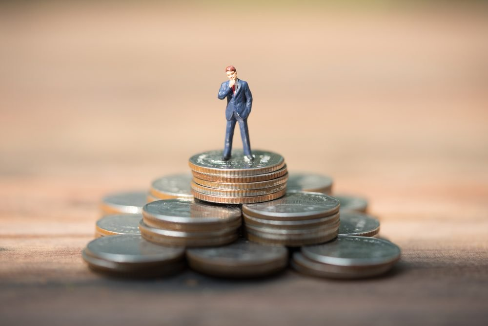 Miniature people, business man standing on stack of coins, financial, savings concept.