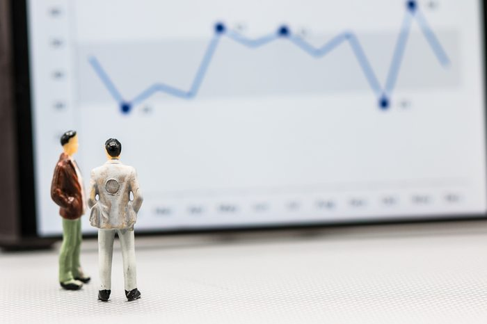 Miniature people : small figures businessmen stand with graph on the phone display with copy space and using as background finance business team competition concept, business plan concept.