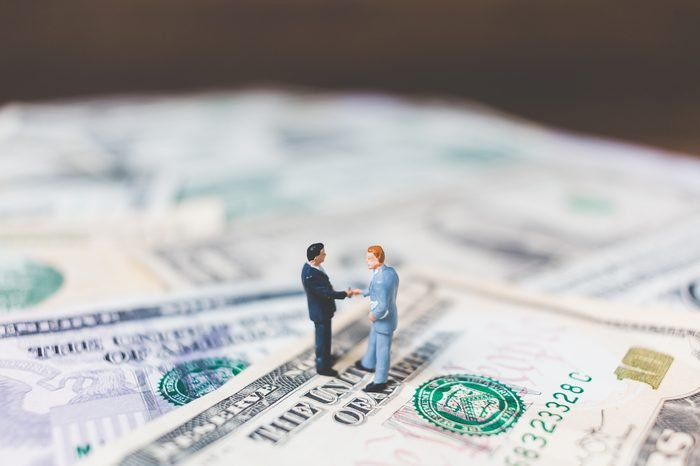 Miniature Business people with US dollar banknote background