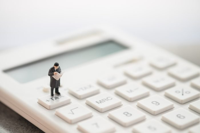 Miniature people: businessman standing on tax button of calculator. Financial, and business concept