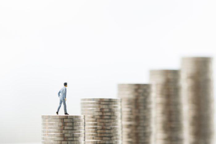 Miniature people: small figure businessman standing on a stack of coins with white background. Money, Financial, Business Growth concept.
