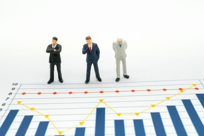 Miniature People: Business man looking at analyst graph with copy space using as background money, financial, business concept.