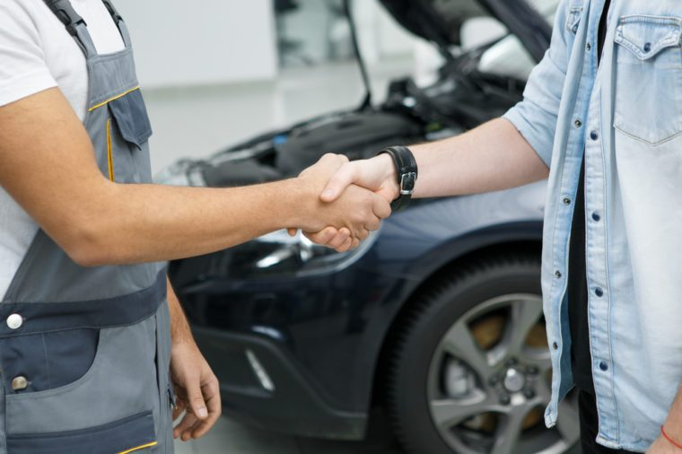 Cropped shot of a professional mechanic shaking hands with his client car on repair on the background partnership agreement deal service people gesture owner professionalism trust experience worker