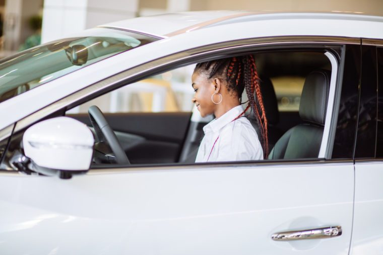 Pretty young woman leaning out of car window