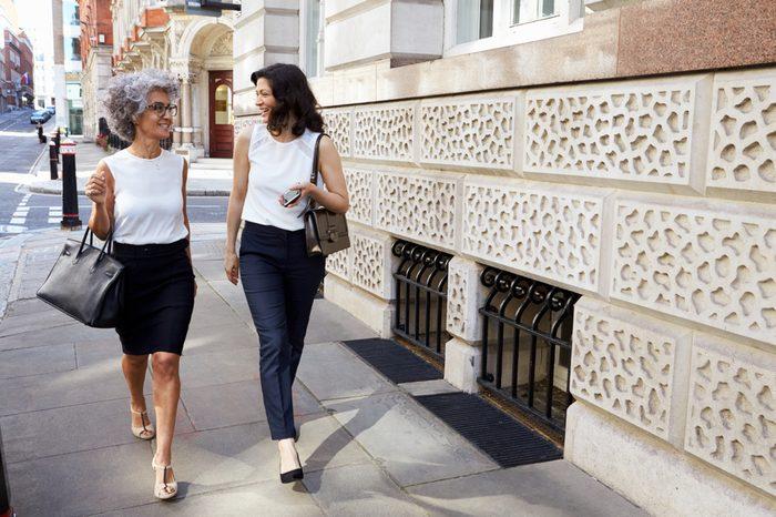 Two women walking in the street talking, full length