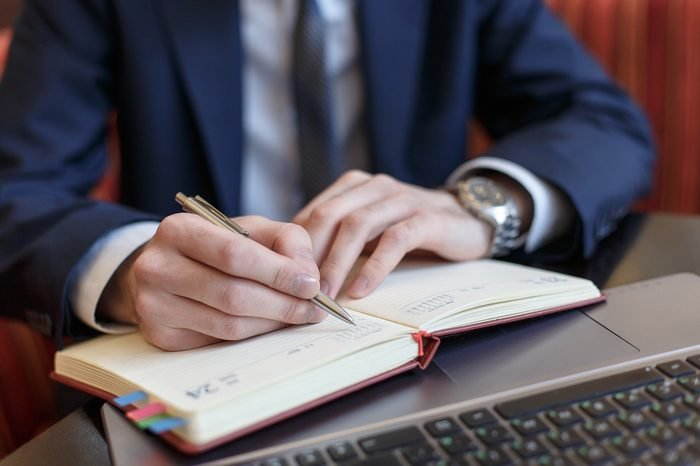 Office worker writing notes in planner book